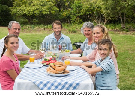 Multi generation family having dinner outside at picnic table smiling at the camera - stock photo