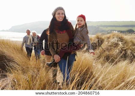 Multi Generation Family In Sand Dunes On Winter Beach - stock photo