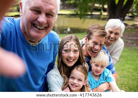Multi-generation family posing for a selfie in the park on a sunny day - stock photo