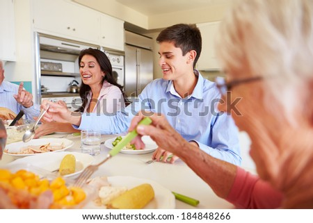 Multi-Generation Family Sitting Around Table Eating Meal - stock photo