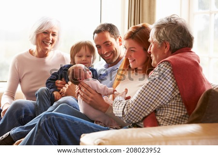 Multi Generation Family Sitting On Sofa With Newborn Baby - stock photo
