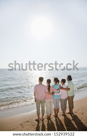 Multi generational family, arms around each other by the beach, rear view - stock photo