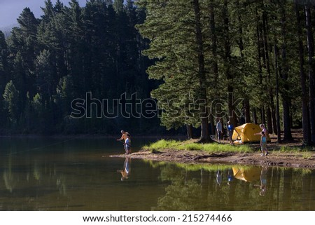 Multi-generational family on camping trip, boy (8-10) and grandfather fishing in lake in mid-distance, side view - stock photo