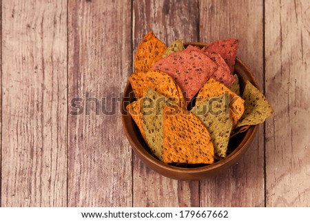 Multi Grain Flax Seed Tortilla Chips In A Wooden Bowl - stock photo