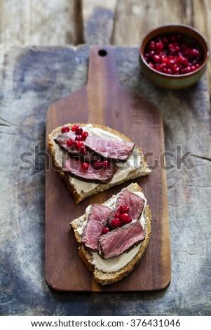 Multi grain sandwich with venison, chestnut puree and lingonberries - stock photo