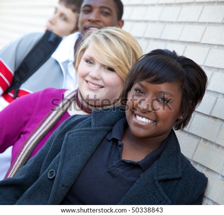 Multi-racial college students, friends outside against a brick wall - stock photo