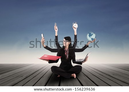 Multi tasking Asian businesswoman  - stock photo