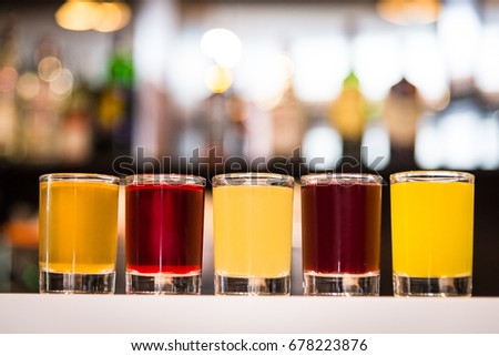 multicolor alcoholic shots on a blurry bokeh background