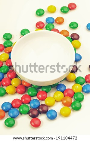 Multicolor candies around a bowl - stock photo