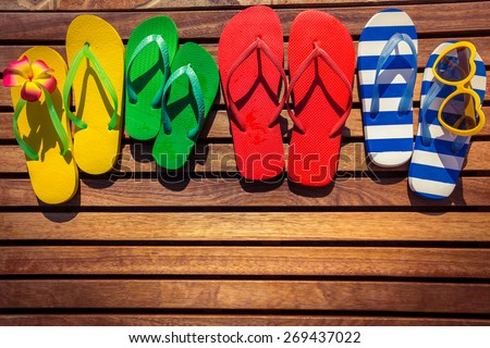 Multicolor flip-flops on wooden background. Summer family vacation concept - stock photo