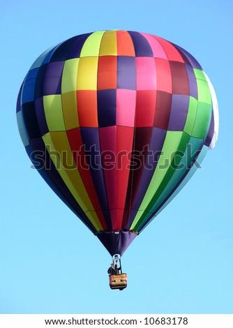 Multicolor hot air balloon over a blue sky - stock photo