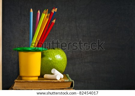 Multicolor pencil, chalk and green apple on old textbook against blackboard in class. School concept - stock photo