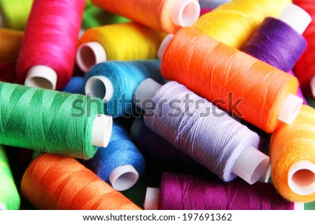 Multicolor sewing threads on wooden background - stock photo