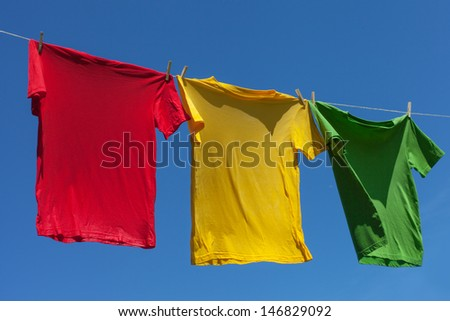 Multicolor shirts on clothesline in sunny day.