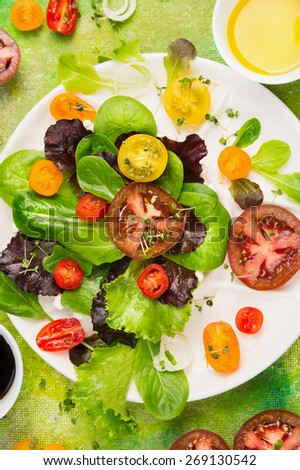 Multicolor Tomatoes various salad in white plate with greens, oil and  balsamic vinegar, top view, close up - stock photo