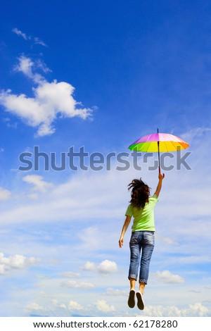 Multicolor umbrella woman jump to sky - stock photo