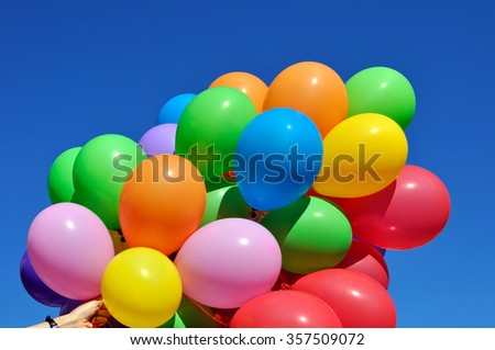 multicolored balloons in the human hand in the city festival on blue sky background - stock photo