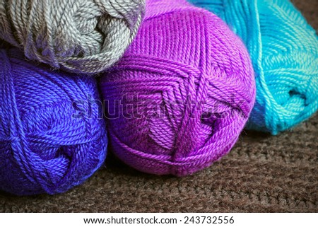 Multicolored balloons of knitting yarn on knitted background - stock photo