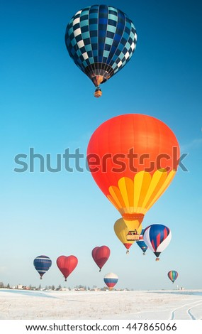 multicolored balloons with baskets over the village in the winter - stock photo