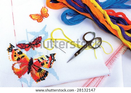 Multicolored butterflies embroidered cross-stitch, canvas for embroidery, threads of floss - stock photo
