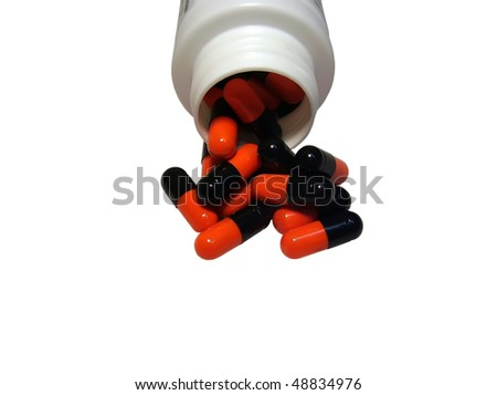 Multicolored capsules out of the bottle on white