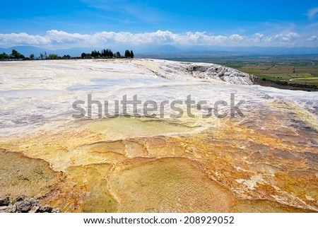 "Multicolored carbonate terraces and travertines with blue water - unique nature wonder in Pamukkale (""cotton castle"" in Turkish), Turkey"