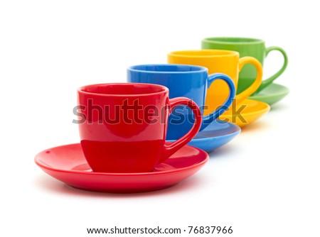 Multicolored ceramic mugs over white - stock photo