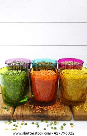 Multicolored clear glasses with various legumes ( green peas, red lentils, canadian lentils, indian lentils, black lentils, green lentils, green mung beans) on white wooden background - stock photo