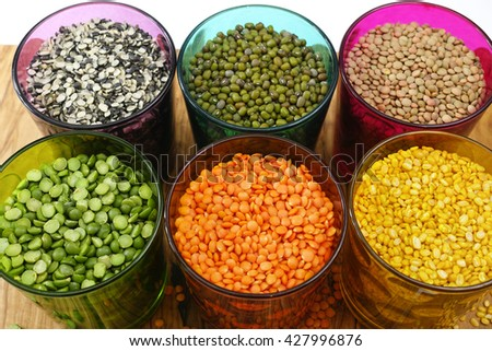Multicolored clear glasses with various legumes ( green peas, red lentils, canadian lentils, indian lentils, black lentils, green lentils, green mung beans) on olive wood background - stock photo
