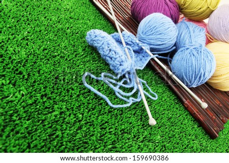 Multicolored clews with needles on grass closeup - stock photo