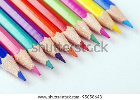 Multicolored crayons in a row on white background. selective focus