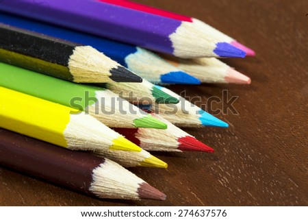 Multicolored crayons on a wooden table - stock photo