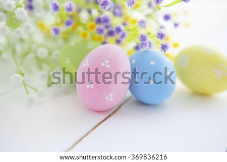 Multicolored Easter eggs in fresh white and yellow flowers daisy. Easter background. Easter symbol. Easter hunt. Copy space - stock photo