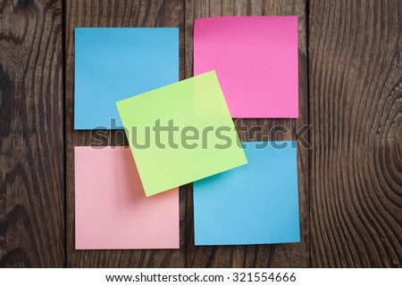 multicolored empty paper sticks for notes hanging on wooden noticeboard - stock photo