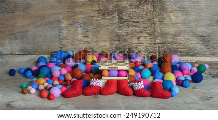 multicolored felted beads, wooden chest and red boots on the wooden background - stock photo