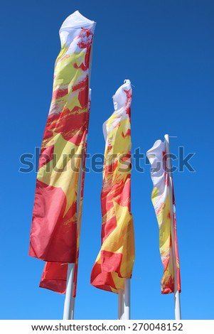 Multicolored festive flags during a holiday against the blue sky - stock photo