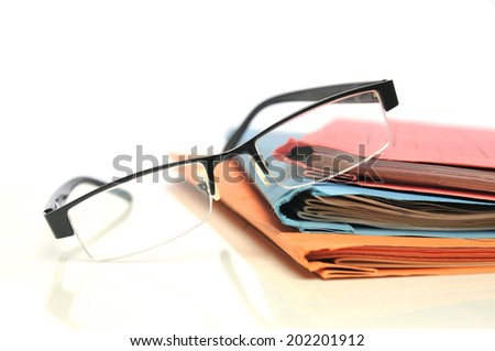 Multicolored folders with glasses on white background - stock photo