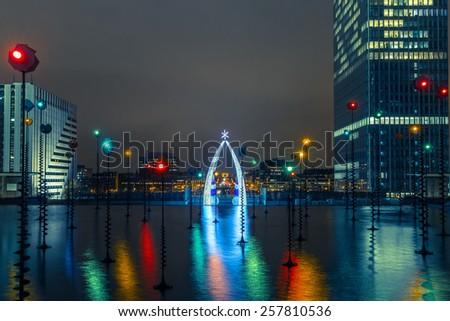 Multicolored fountain and illuminated Arc de Triomphe, view from the Esplanade De La Defense at night in Paris, France - stock photo