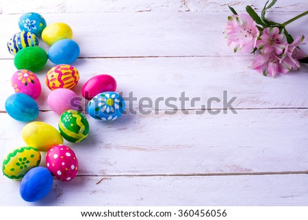 Multicolored hand-painted Easter eggs and pink flowers on white wood plank. Easter background. Easter symbol. Top view with copy space - stock photo