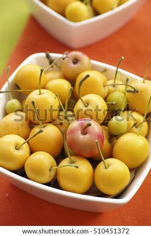 Multicolored little apples in white bowl on orange tablecloth