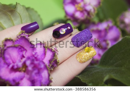 Multicolored manicure with rhinestones and sequins on the background color of violets. - stock photo