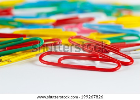 Multicolored office paperclips on white desktop close up - stock photo