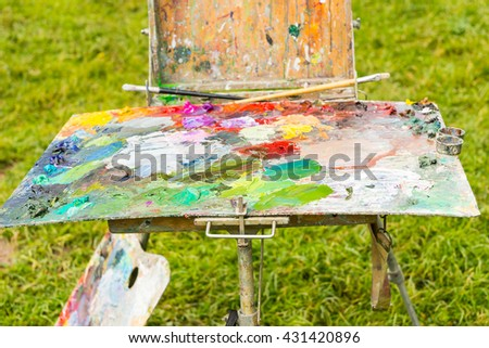 Multicolored  palette of blended oil paints with professional paintbrushes on atist's sketchbook in the forest - stock photo
