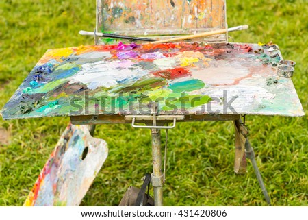 Multicolored  palette of blended oil paints with professional paintbrushes on painter's sketchbook in the garden - stock photo