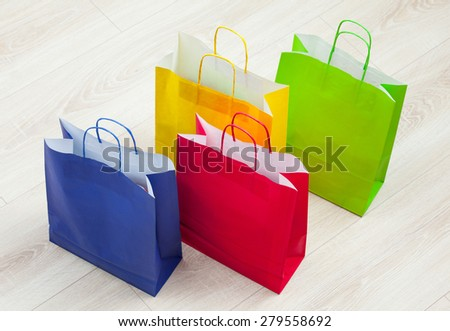Multicolored paper bags on the floor - stock photo