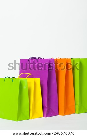 Multicolored paper bags on white background - stock photo