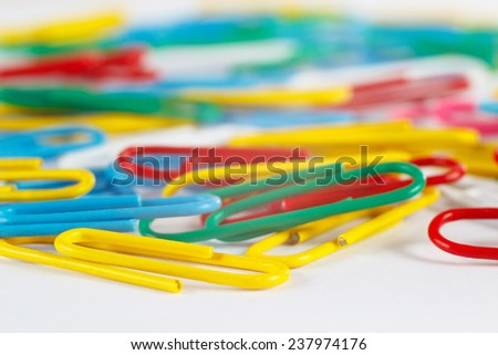 Multicolored paperclips on white desktop close up - stock photo