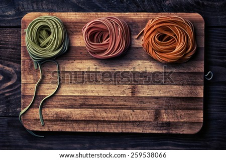 Multicolored pasta rolls on chopping board - stock photo