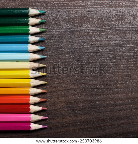 multicolored pencils on brown wooden table background - stock photo