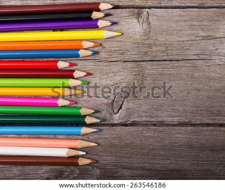 multicolored pencils on the wooden background - stock photo